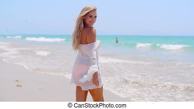 Young Happy Woman Walking on The Beach Wearing White Dress...