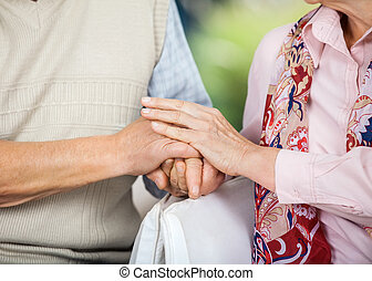 Senior Couple Holding Hands While Sitting On Chairs -...