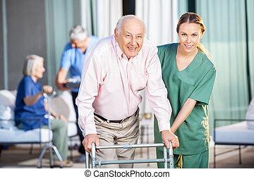 Female Caretaker Helping Senior Man In Using Zimmer Frame -...