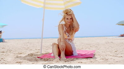 Pretty Young Woman Sitting Under Beach Umbrella - Pretty...