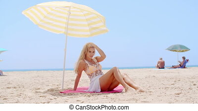 Pretty Young Woman Sitting Under Beach Umbrella