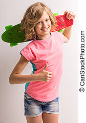 Freestyle - Cute girl standing with skateboard behind her...