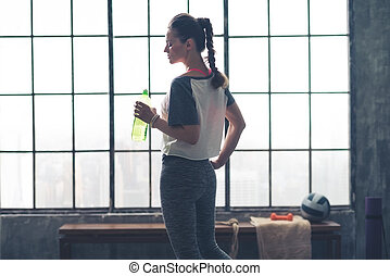 Profile view of fit woman holding water bottle in loft gym -...