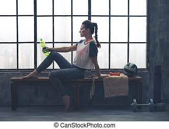 Fit woman sitting on bench in loft gym holding water bottle...