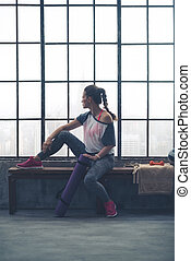 Fit woman sitting on loft gym bench looking out window - A...