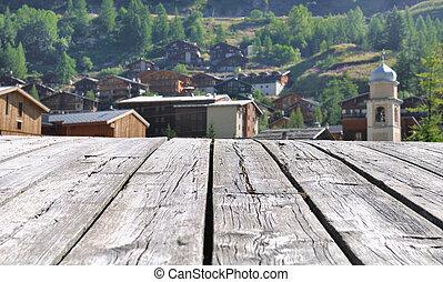 Savoy village bordering the boards of a wooden bridge