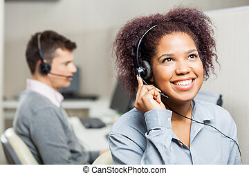 Happy Female Call Center Agent Using Headset In Call Center...