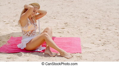 Sensual Woman Sitting on the Mat at the Beach - Sensual...