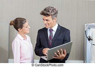 Manager And Call Center Employee Using Laptop - Smiling...