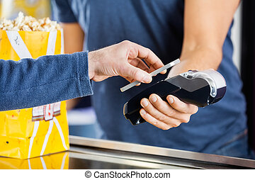 Man Making Payment Through NFC Technology At Cinema -...