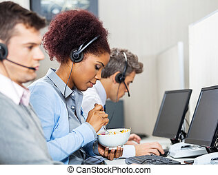 Female Customer Service Representative Having Food In Office...