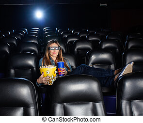 Woman Holding Snacks While Watching 3D Movie At Theater
