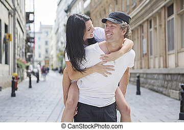 Man giving piggyback ride to girlfriend, having fun - A Man...