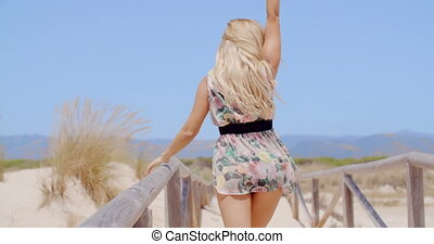 Rear View of a Sexy Woman Walking on Beach Pathway