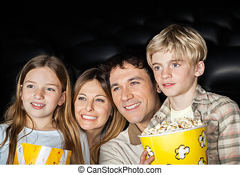 Happy Family Watching Film In Movie Theater