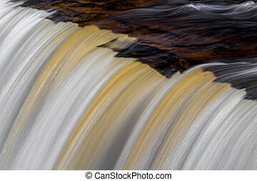 Tahquamenons Edge - Tannin-stained whitewater pours over the...