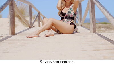 Blond Woman at Sandy Beach  she Sitting on Wooden Footbridge