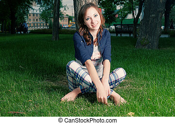 Young teenage girl sit cross legged on spring grass smiling