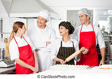 Cheerful Chefs Conversing In Commercial Kitchen - Cheerful...