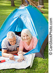 Senior Couple Studying Map At Campsite - Portrait of senior...