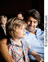 Smiling Family Watching Movie In Theater