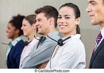 Customer Service Representative Standing With Colleagues And...