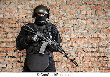Special forces operator in black uniform and bulletproof