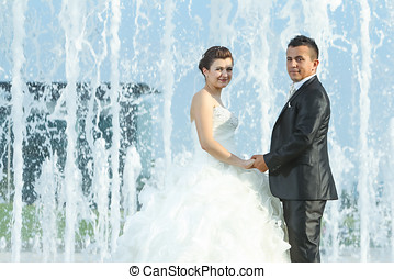 Married couple in front of water fountain