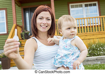 Mother and baby in front of the house - A Mother and baby in...