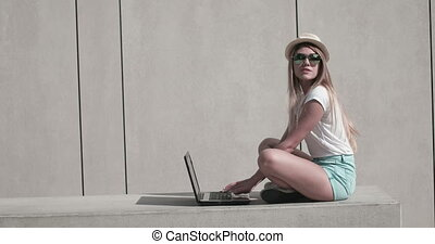 Woman On Bench Using Laptop - Attractive young woman sat on...