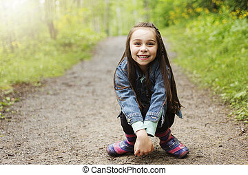 Adorable little girl in the forest meadow
