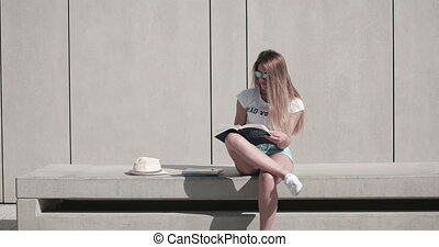 Woman On Bench Reading Book - Attractive young woman sat on...