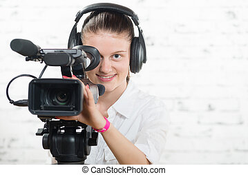 a pretty young woman with a professional movie camera and...