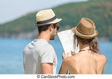 a young couple on holiday looking at a map