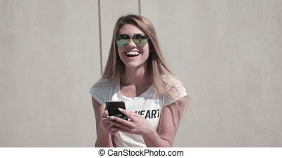 Woman Smiling Whilst Using Phone - Attractive young woman...