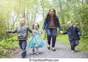 family in forest having fun together - A family in forest...