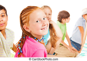 Red smiling girl turning back with her friends