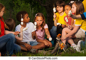 Group of children with s'mores near bonfire - Group of...