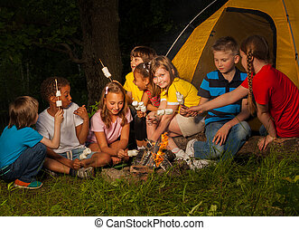 Campers sitting with marshmallow near bonfire - Teens sit...