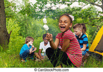 Laughing African girl holds stick with smores - Laughing...