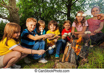 Happy friends near bonfire with marshmallow during camping...