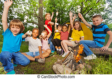 Teens with arms up near bonfire hold marshmallow - Teenagers...