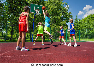 Team in colorful uniforms playing basketball game on the...