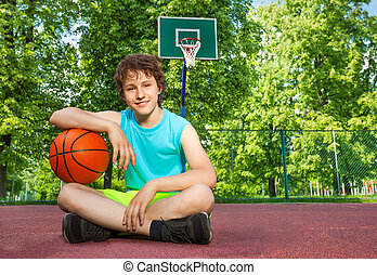 Boy sitting alone with elbow on the ball - Boy sitting on...