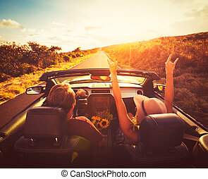Couple Driving Convertable at Sunset - Young Couple Driving...
