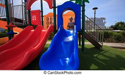 little girl with hairtails tries to slide down on playground