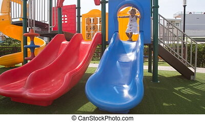 little girl with hairtails climbs up slides down on playground