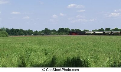 Steam train running in rural landscape - wide shot - Steam...