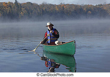 Man Paddling a Canoe with a Small White Dog in the Bow - Man...