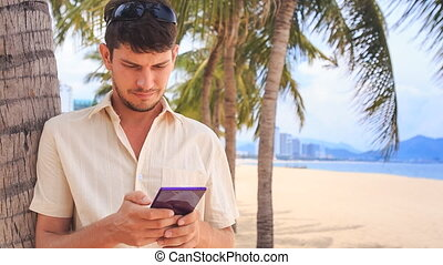 guy in white operates iphone under palm tree on sand beach -...